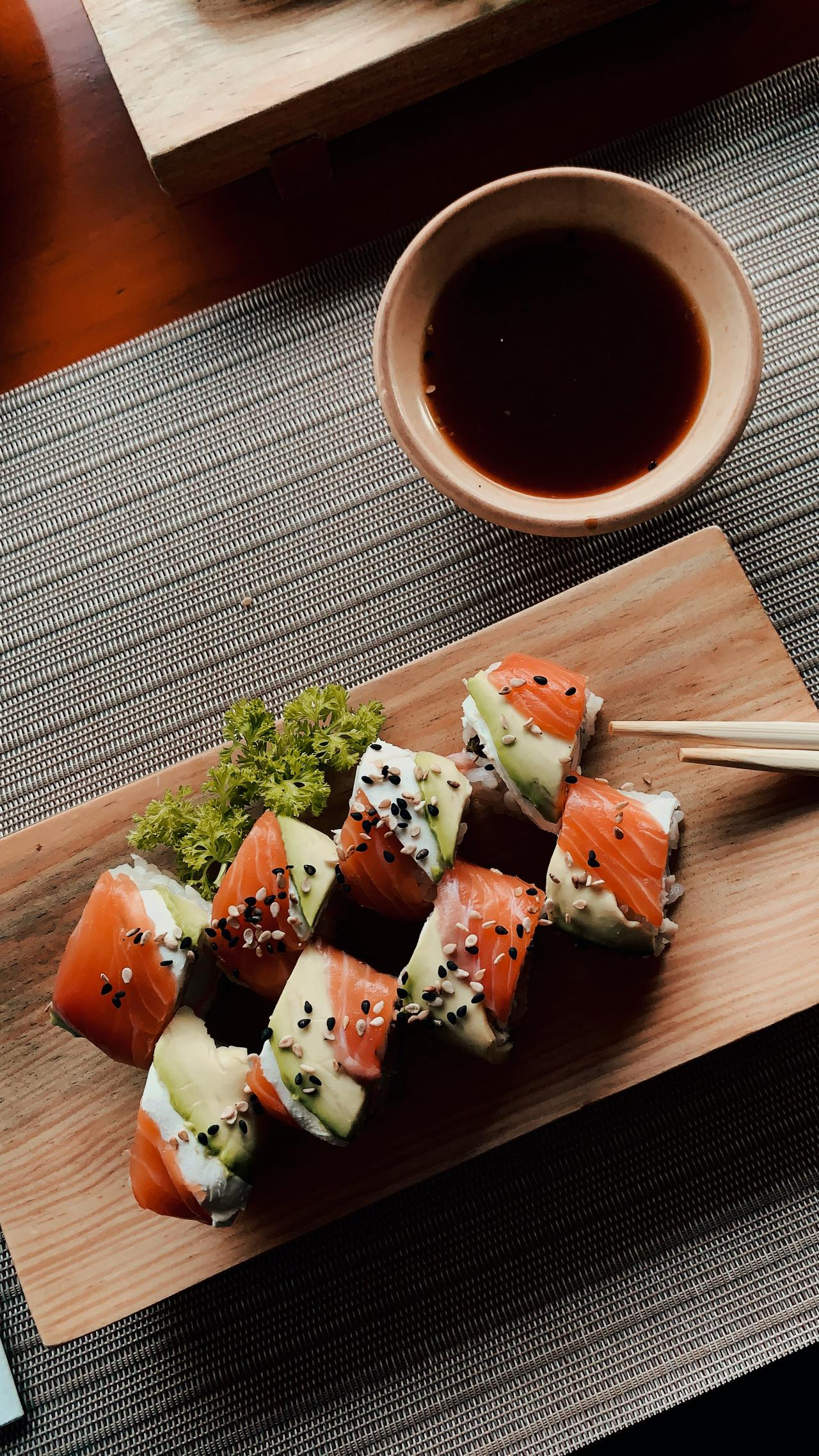 Sushi on a wooden plate with chopsticks resting against it and soy sauce nearby in a dish.