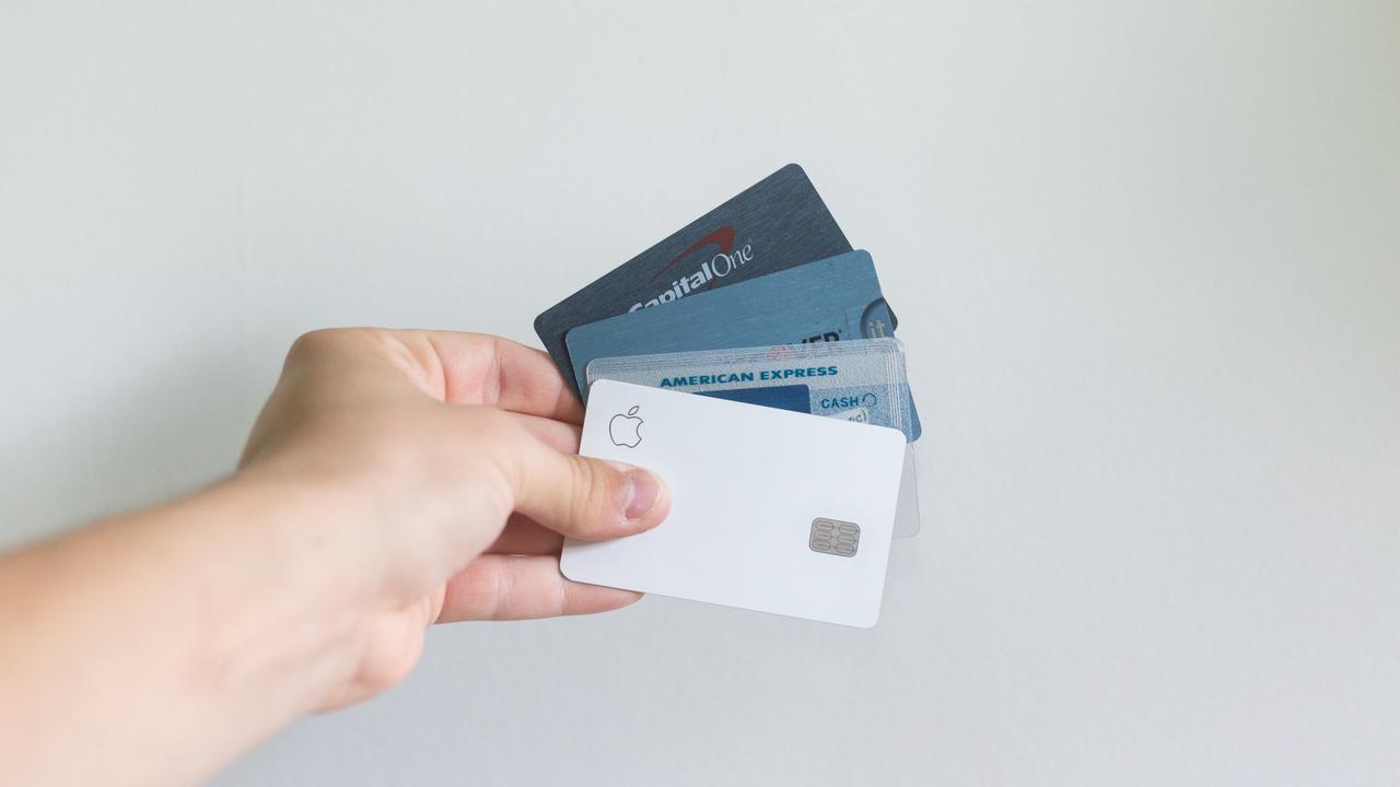 A person holding credit cards against a white background wall.