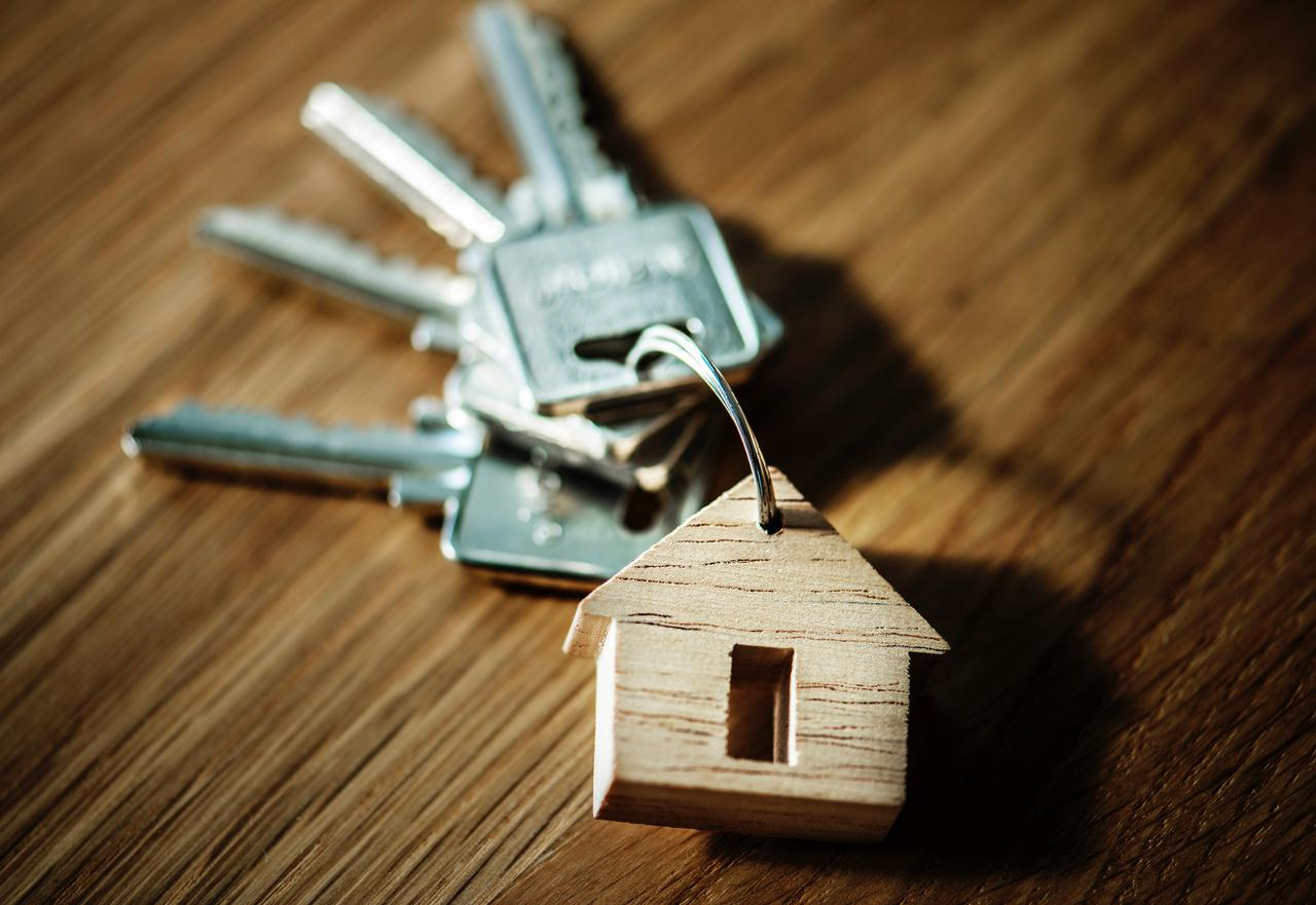selective focus photography of four silver keys with brown house keychain on brown surface