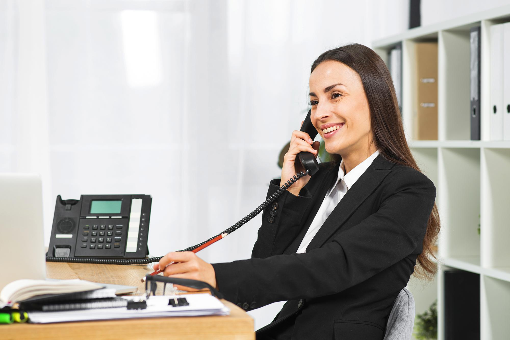 young-businesswoman-smiling-while-talking-telephone-office.jpg