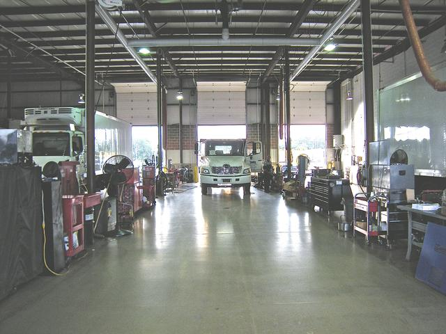 epoxy coating floor in a garage with trucks