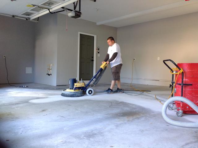 man working on a concrete garage floor coating
