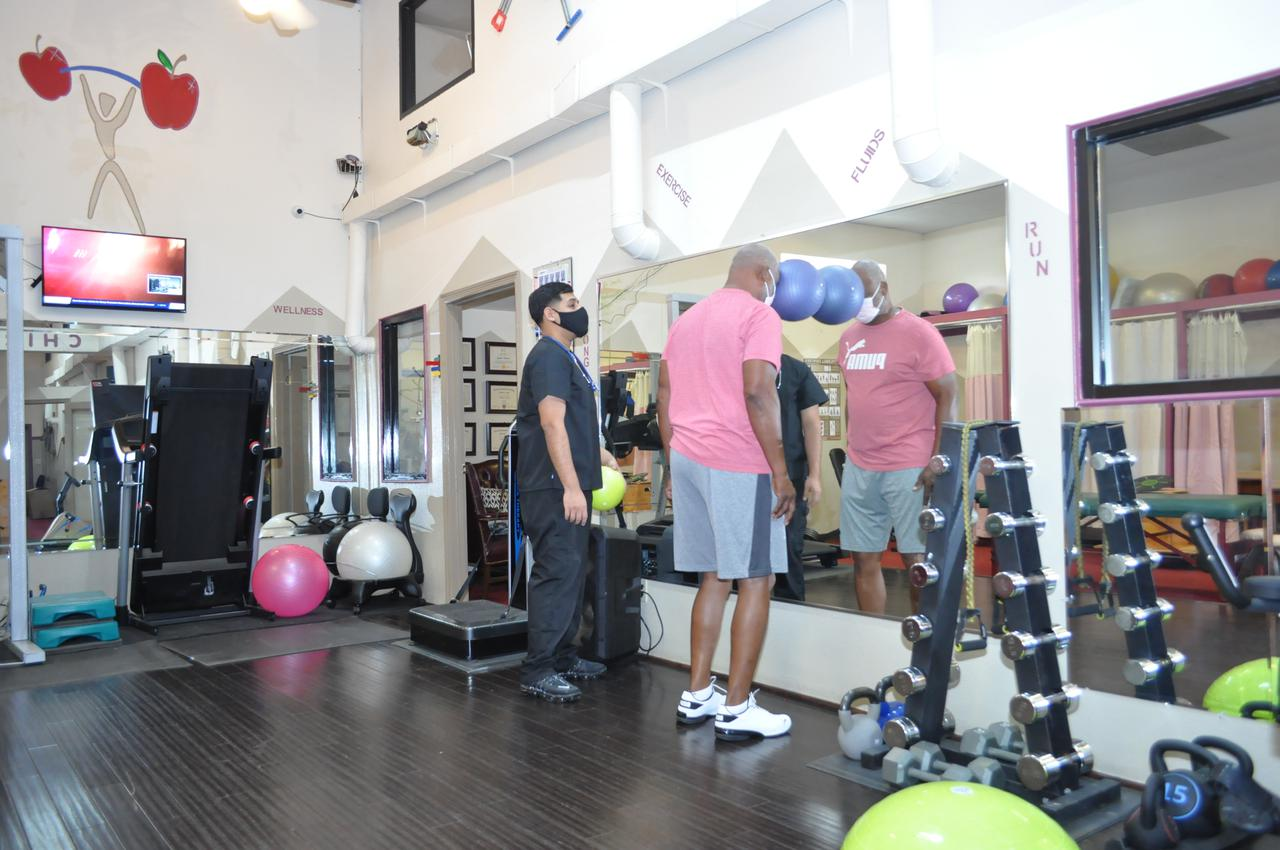 patient and care team member working out at healthcare solutions chiropractic care center in houston tx
