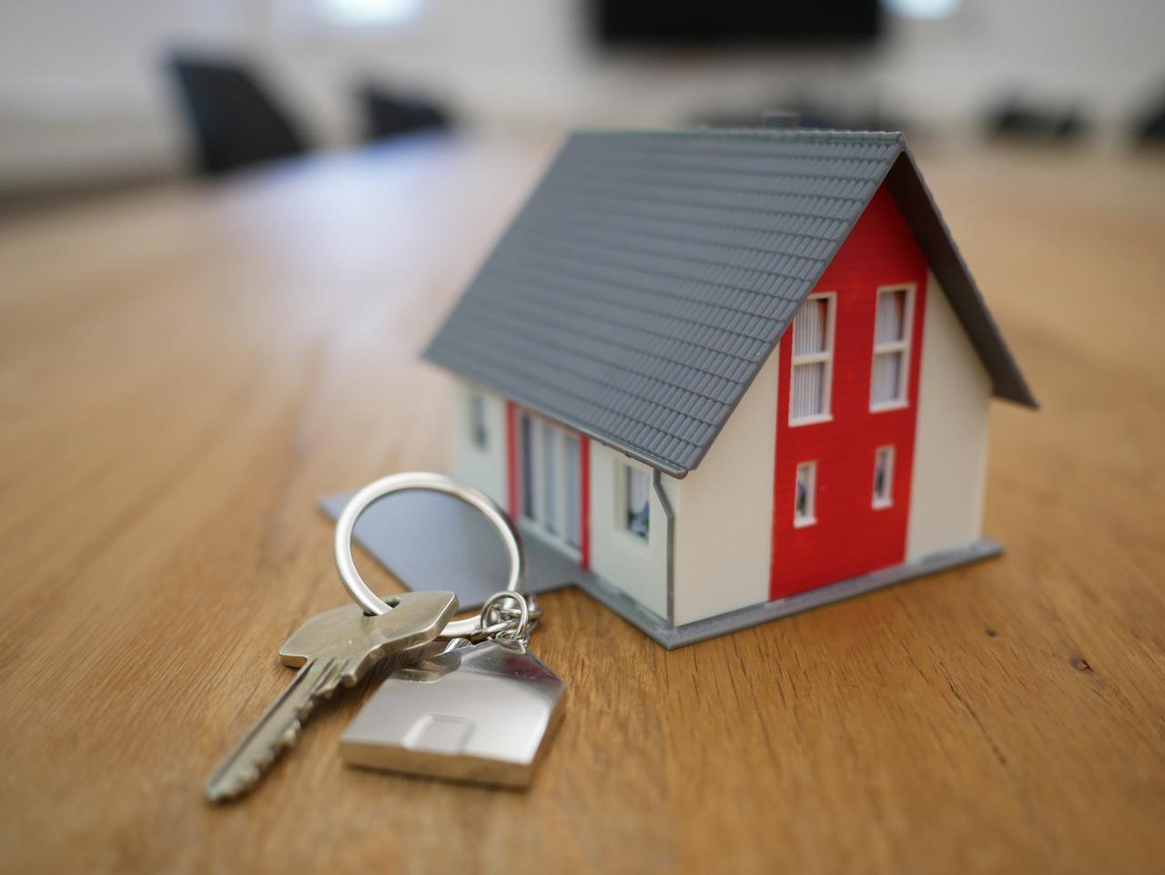 model house next to a set of keys on a desk