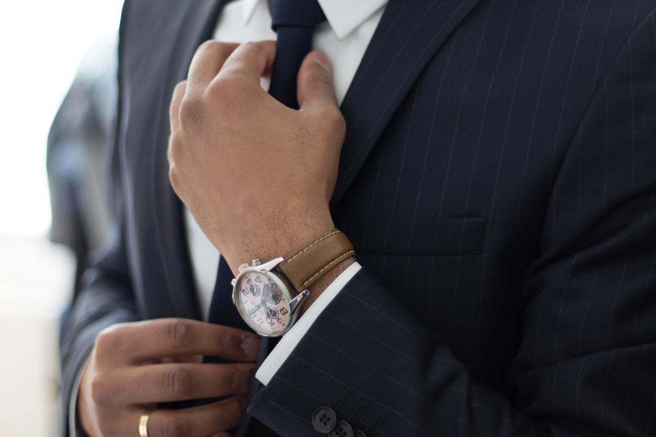 a man adjusting the tie on his suit