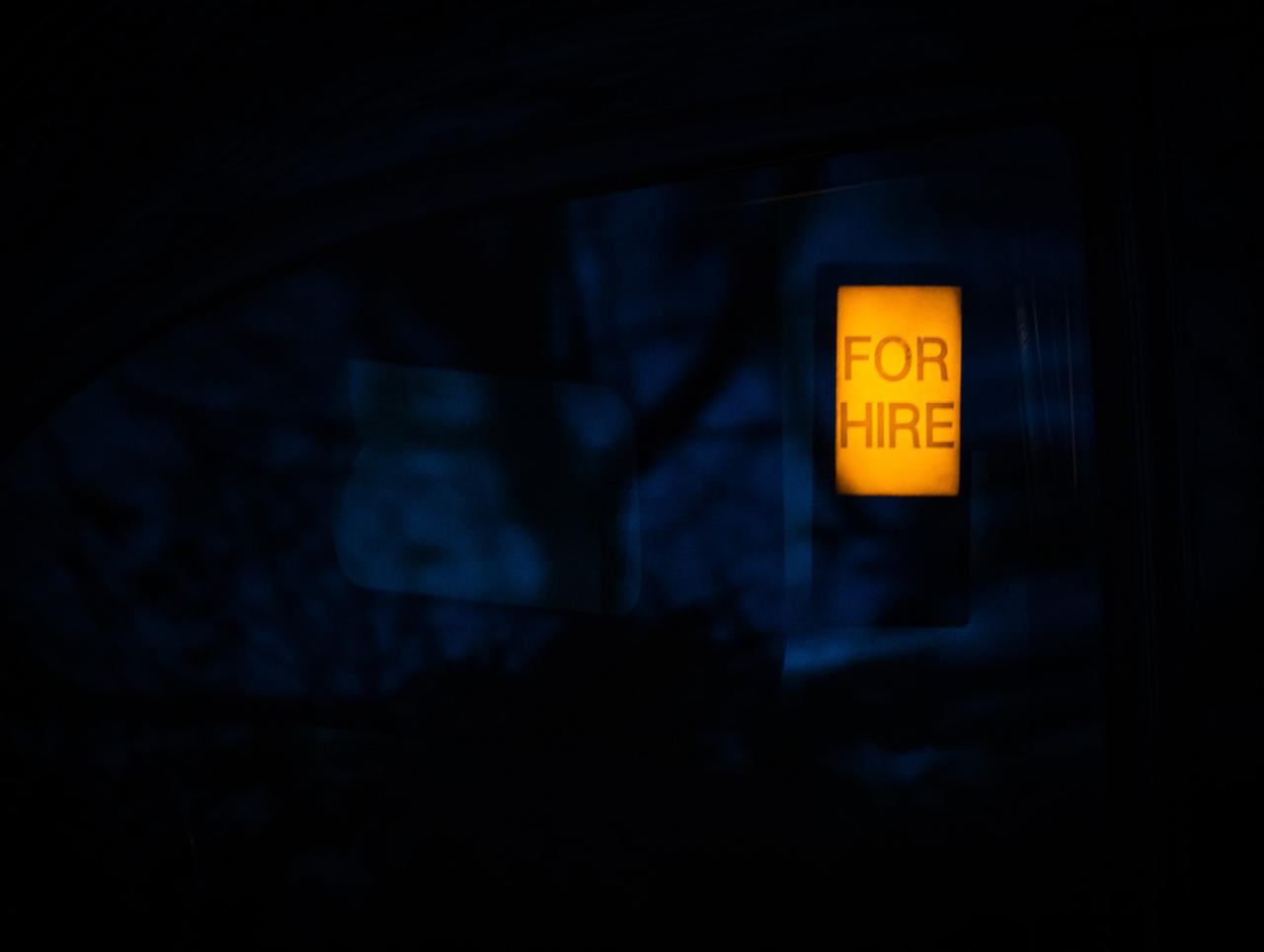 "Illuminated orange ""For Hire"" sign on a night blue background."