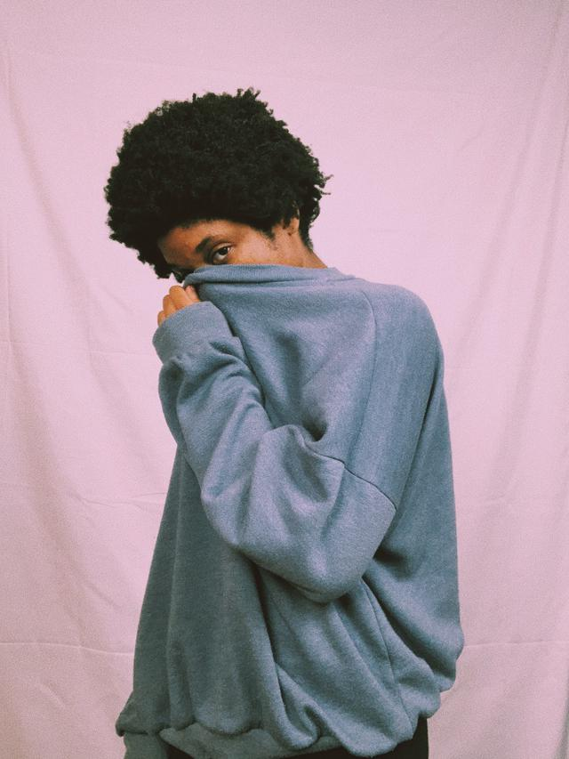 A woman holding a sweater over her nose. With the help of a psychiatrist and medication management, depression can be overcome.