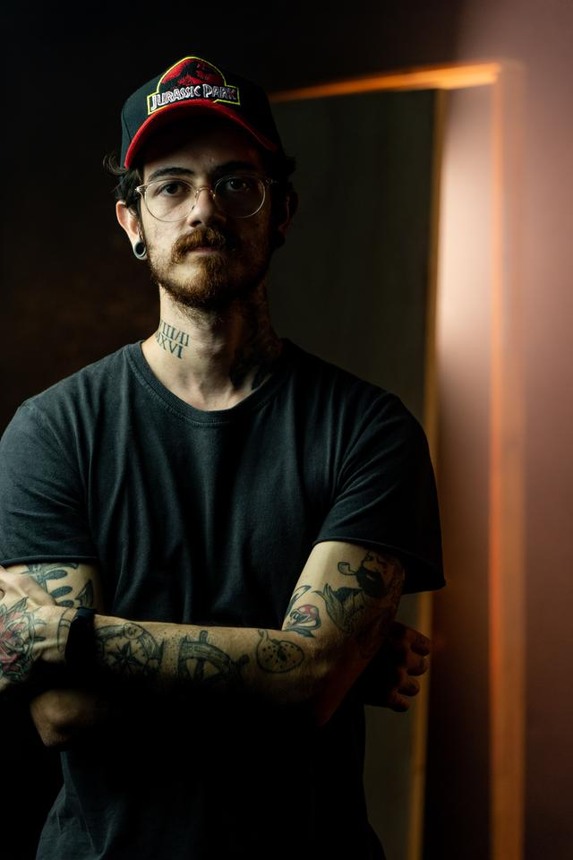 A man with a cap and tattoos staring into the camera. Medication management in Portland, OR can revolutionize your life.