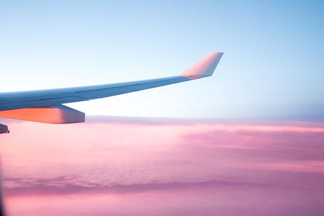 shot of an airplane wing in the sky against a background of blue skies and pink clouds