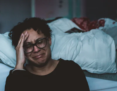 a young woman crying by her bedside.png