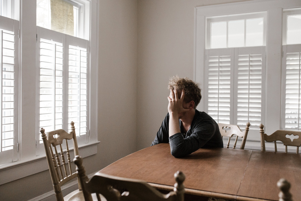 a depressed man sitting at a table..png