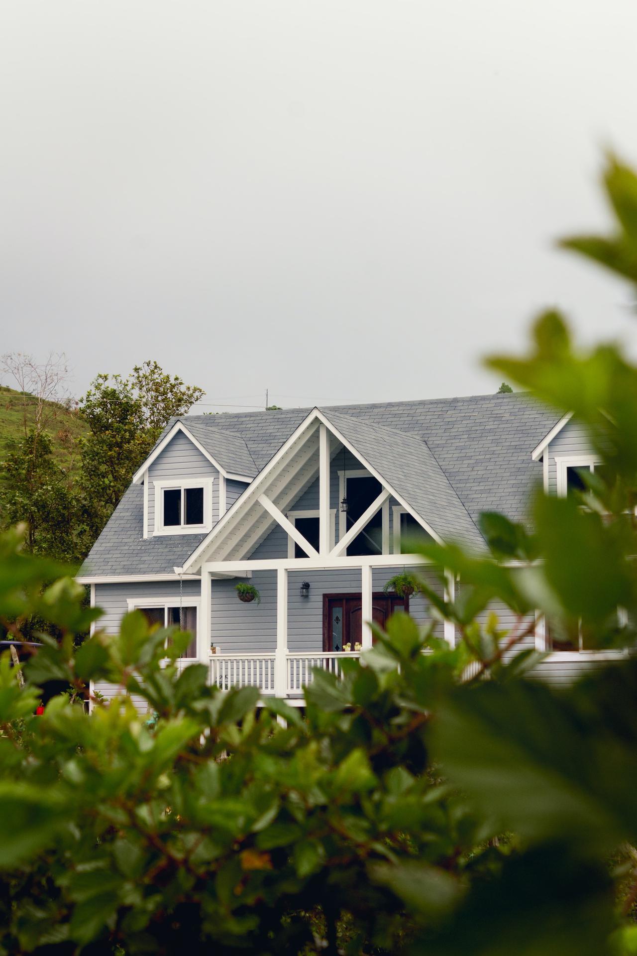 Grey house behind green bushes.