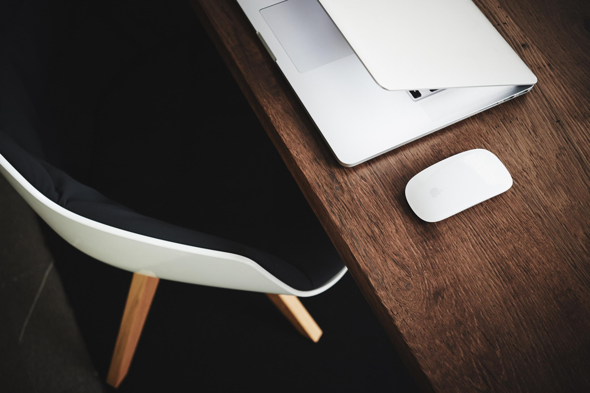 laptop and mouse sitting on a brown wooden desk
