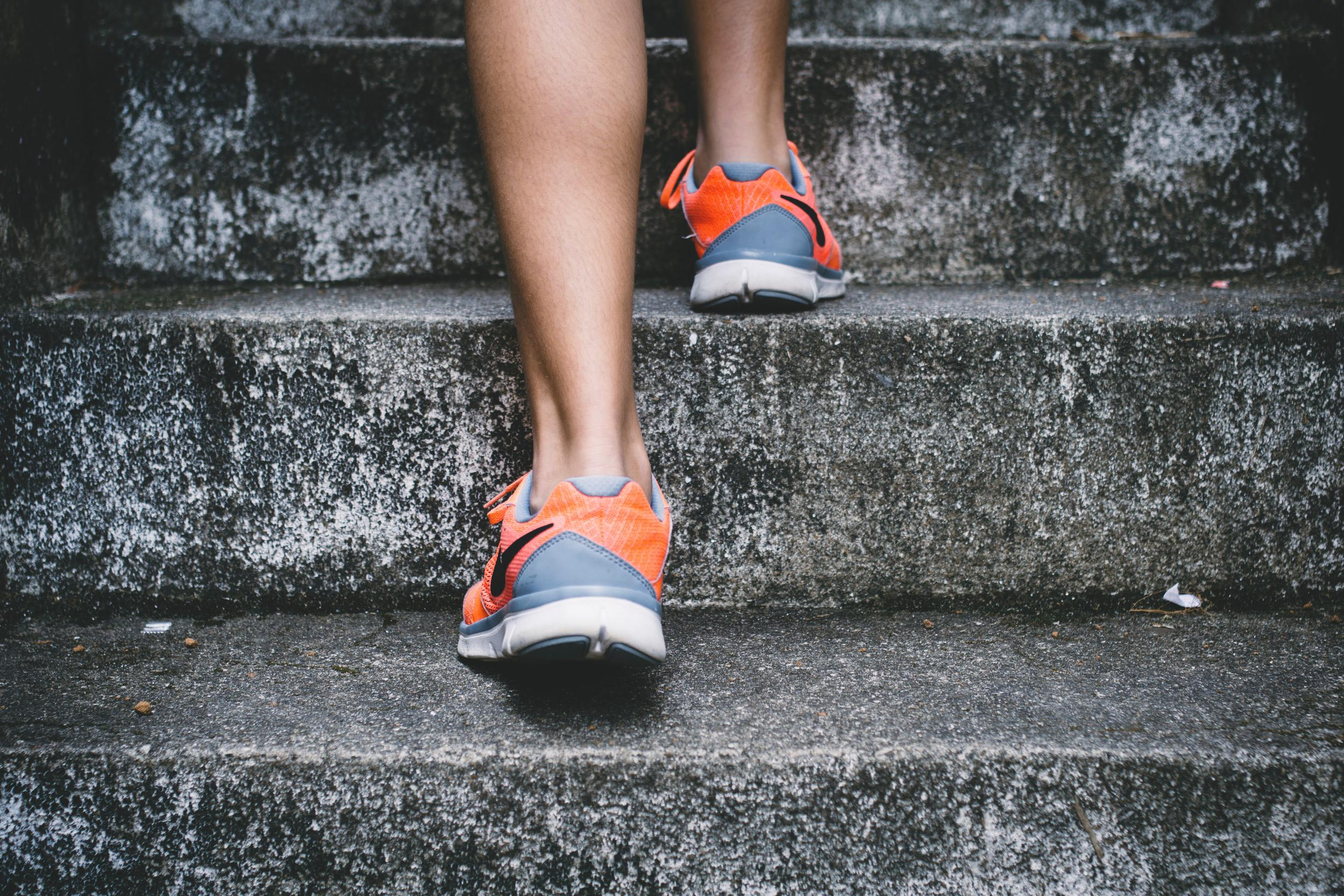 image of a woman's fitness shoes walking up concrete steps