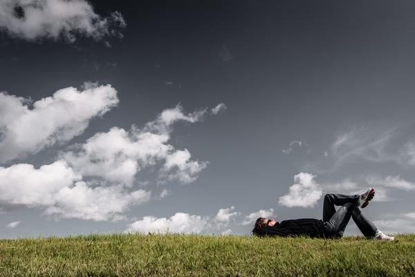 man lying on grass with hands on head