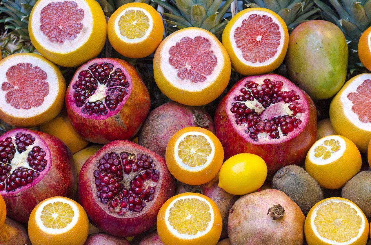6 orange fruit beside lemon and red round fruit