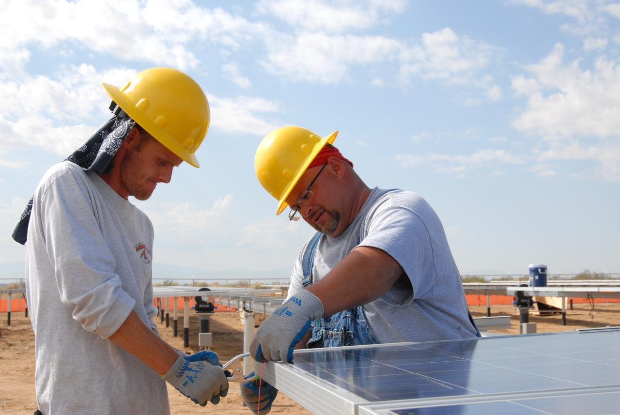 two men working on a solar panel