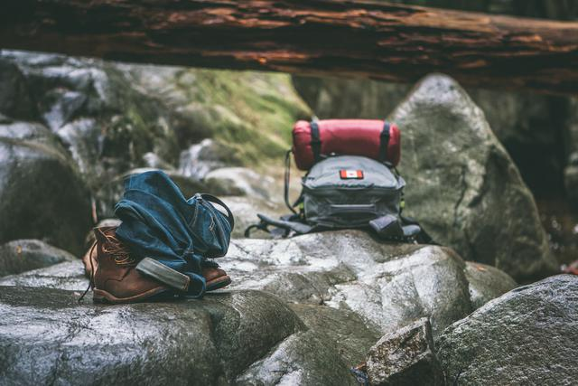 A bookbag, jeans, and boots left on a rock while their owners swim in a river.