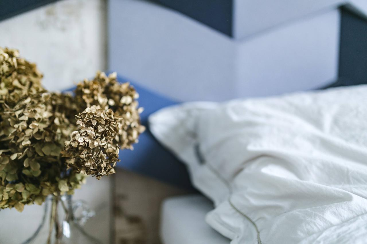 3caaa70e-a48f-11e7-b252-0242ac110002-kaboompics_An_ornamental_golden_plant_in_a_jar_by_the_bed_with_white_sheets.jpg