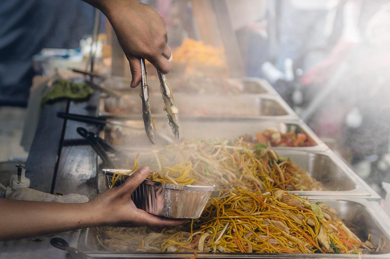 A street vendor doling out noodles.