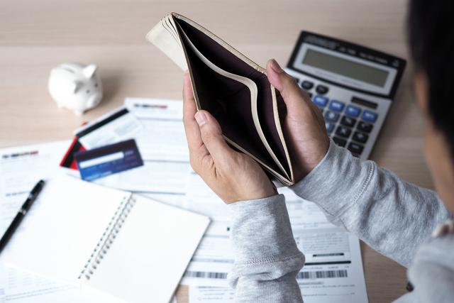 ef9977b0-659c-11eb-a722-0242ac110002-hands-open-empty-purse-after-calculating-cost-from-credit-card-bill-debt-concept.jpg